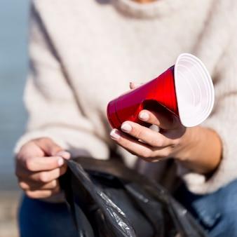 海辺でのクローズアップのプラスチックカップ