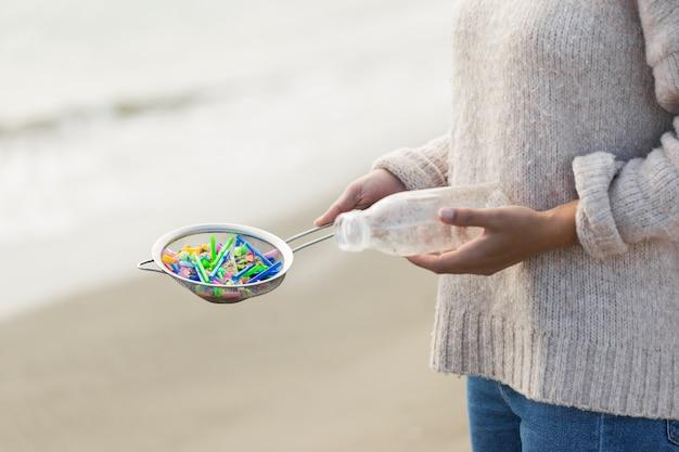 Женщина держит сито с пластиком