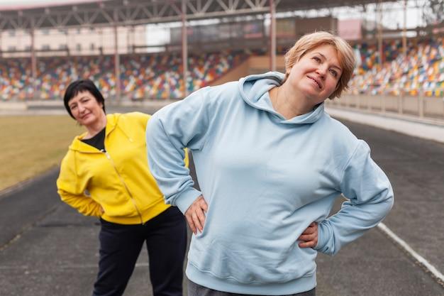 スタジアムでストレッチする高齢者の女性