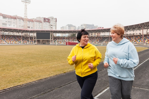 Старшие женщины бегают на стадионе