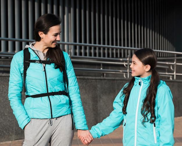 Мать и дочь в спортивной одежде, держась за руки