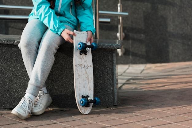 Маленькая девочка держит скейтборд рядом с ней