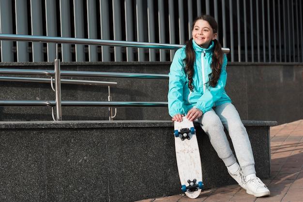 Маленькая девочка держит скейтборд рядом с ней с копией пространства