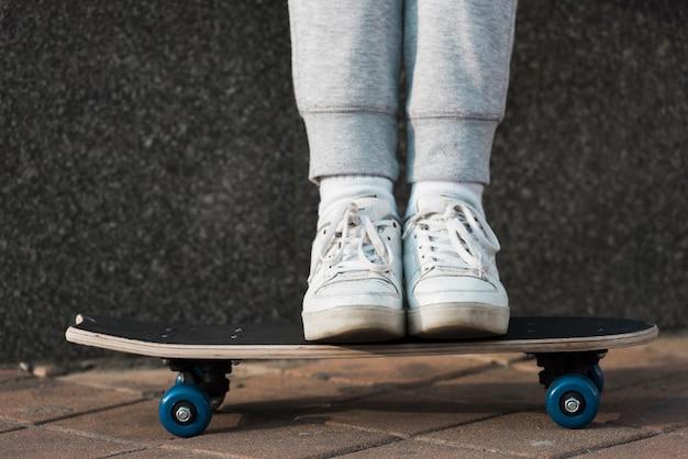 Маленькая девочка стоит на скейтборде