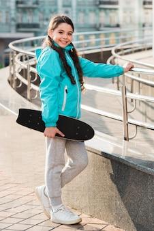 Маленькая девочка держит в руке скейтборд