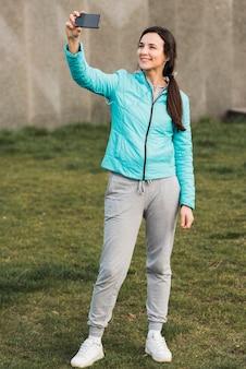 Женщина в спортивной одежде, принимая селфи