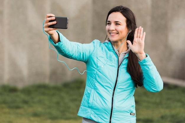 Женщина в спортивной одежде, принимая селфи снаружи