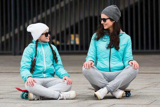 Мама и дочка сидят на скейтборде