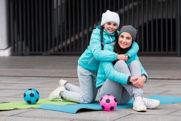Мать и дочь на коврике обнимаются
