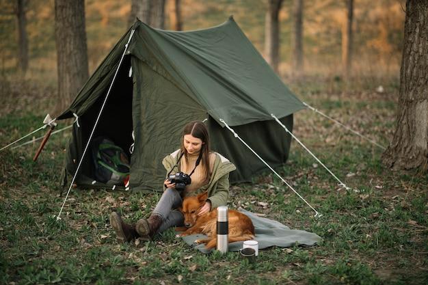テントの近くのカメラを持つ女性