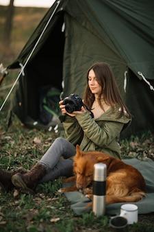 テントの近くのカメラを保持している女性