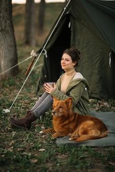 テントの近くのフルショットスマイリー女性