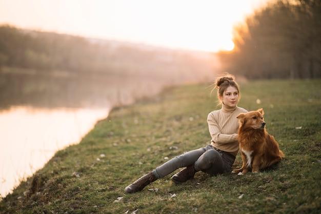犬と一緒に座っているフルショットの女性