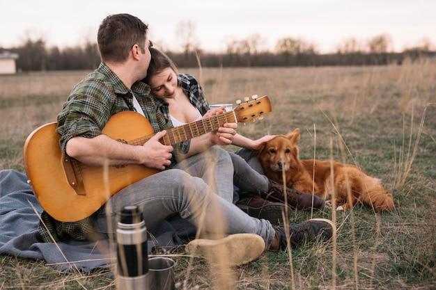 Пара с гитарой и собакой