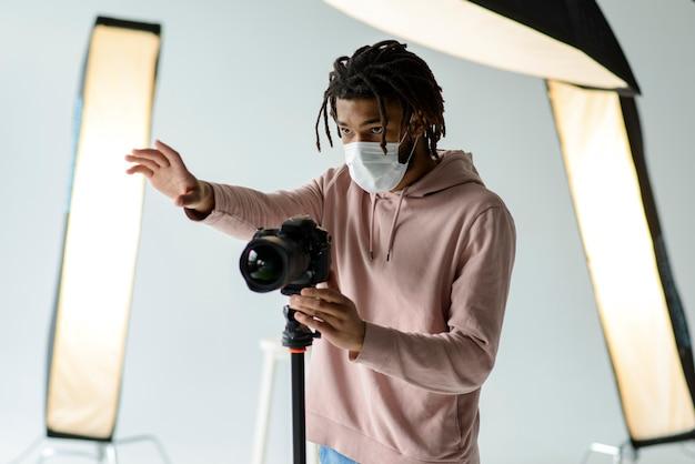 医療用マスクを持つカメラマン