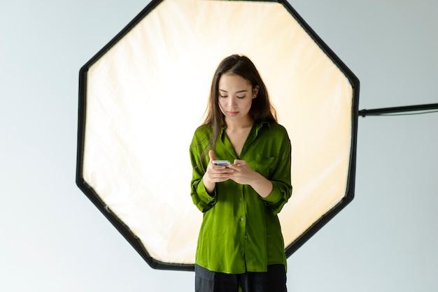 スマートフォンを保持しているミディアムショットの女性