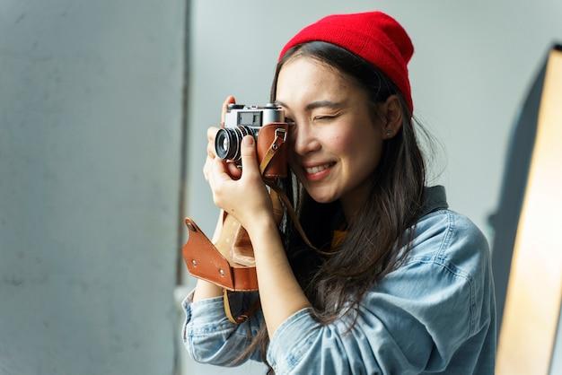 小さなカメラを持つ女性のカメラマン