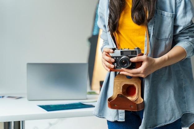 小さなカメラを保持しているクローズアップの女性