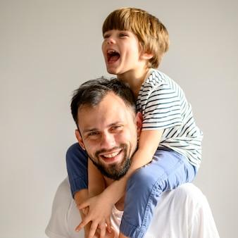ミディアムショットの幸せな父と息子