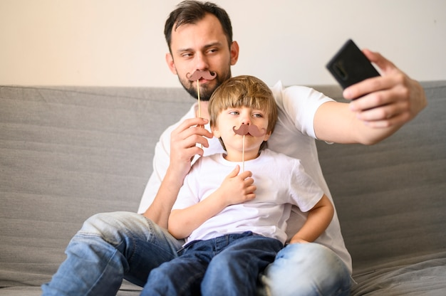 Отец и сын, принимая селфи