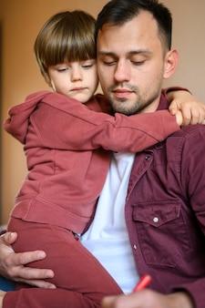 ミディアムショットの子供を抱き締める父