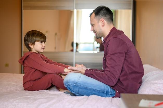 フルショットの息子と父親が手を繋いでいます。