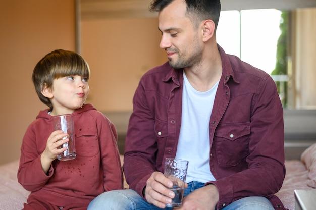 Отец и сын пьют воду