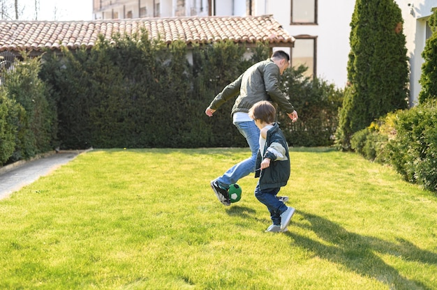 Полный выстрел отец и ребенок, играя на открытом воздухе