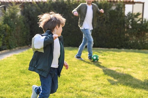 Отец и сын играют с мячом
