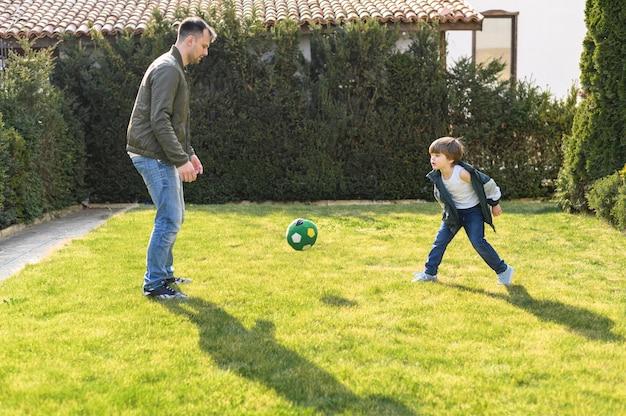 Отец и ребенок играют с мячом