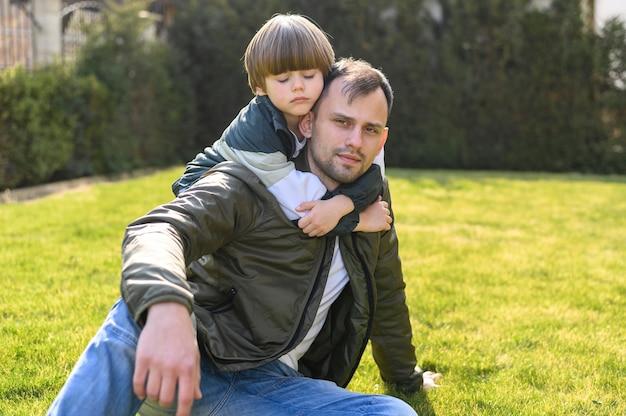 Малыш держит отца на открытом воздухе