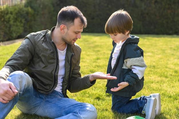 Малыш и отец сидят на траве