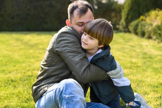 Малыш и отец обнимаются на траве