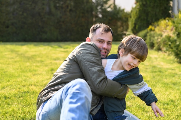 Малыш и отец играют на траве