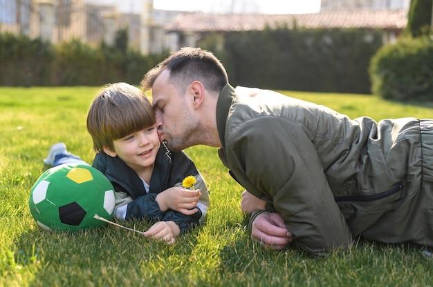 Отец целует сына на улице