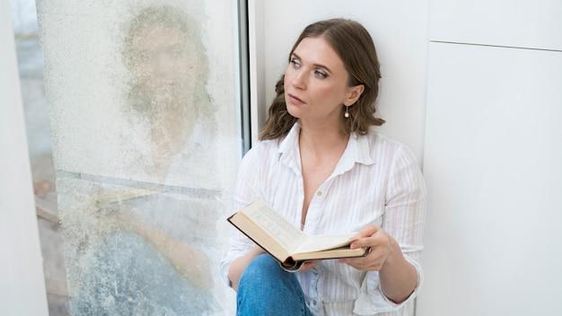 本とミディアムショットの女性