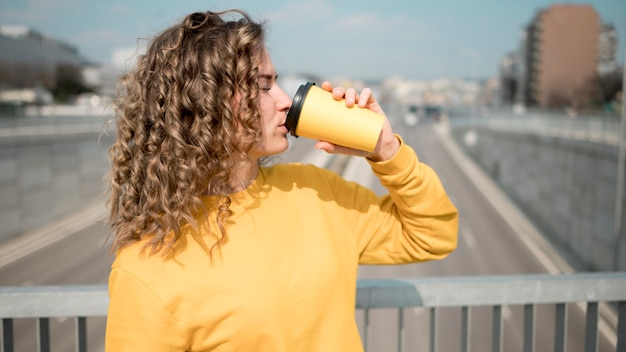Женщина в желтой рубашке пьет кофе