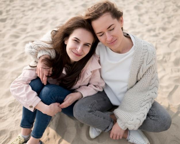 Высокий вид женщин, сидящих на пляже