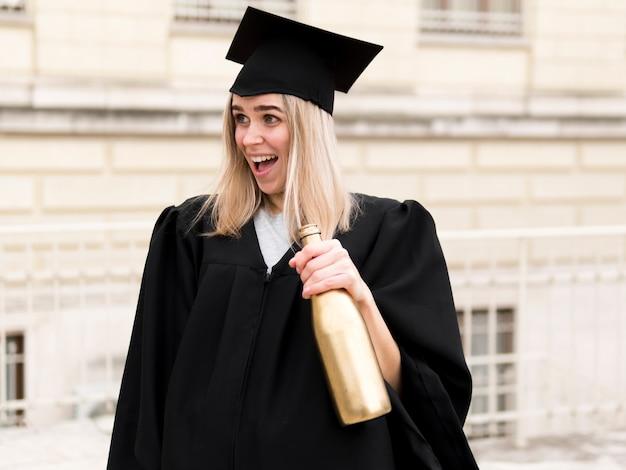 卒業式のガウンのスマイリーの若い女性