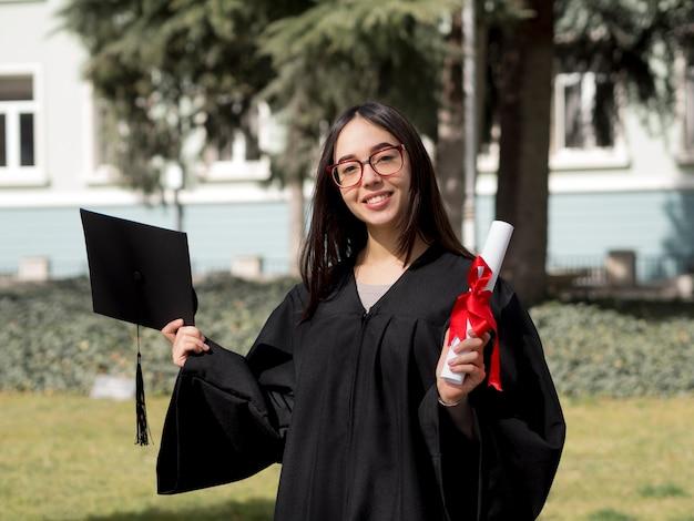 卒業式のガウンを着ている正面の若い女性