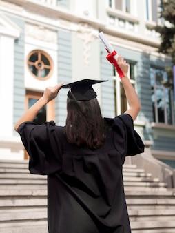 屋外の卒業式のガウンを着ている若い女性を背面します。