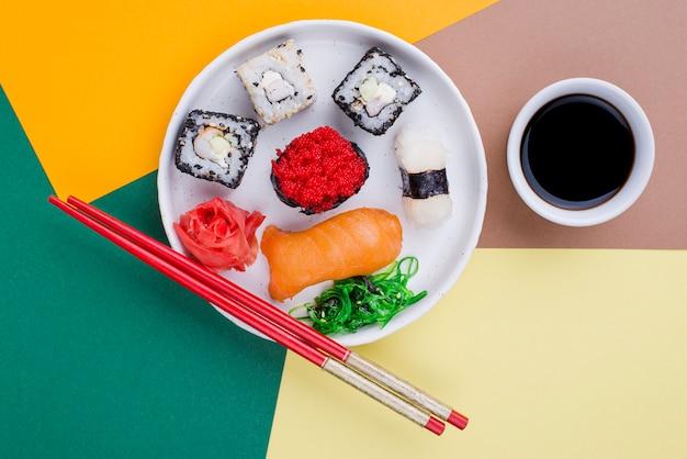 Плоская тарелка с суши и соусом