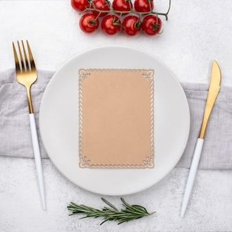 Тарелка со столовыми приборами и помидорами
