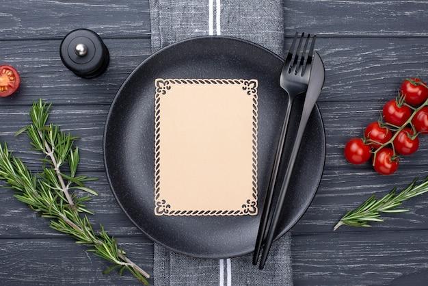 Плоская тарелка со столовыми приборами и помидорами