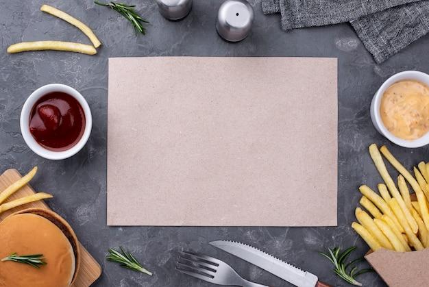 ハンバーガーとフライドポテトの横の紙