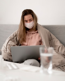 Женщина, носящая медицинскую маску, используя свой ноутбук