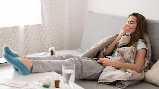 ベッドに座っている病気の女性
