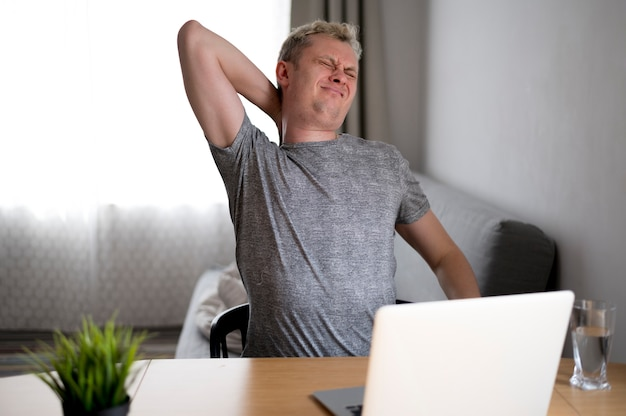 家に座っている背中の痛みを持つ男