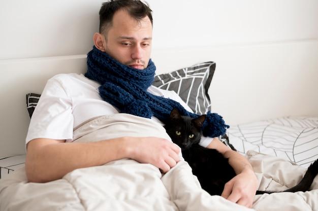 黒い子猫を保持している病気の人