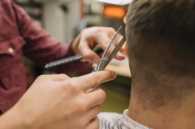 クライアントに散髪を与えるクローズアップのヘアスタイリスト